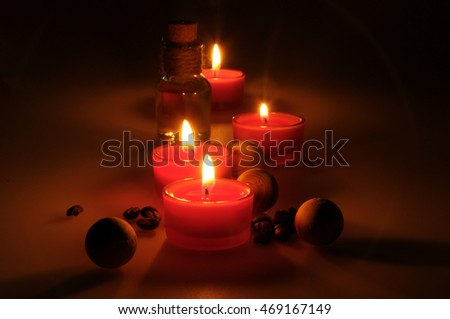 spa composition. scented candles, coffee beans, aromatic wooden balls and oil in a glass jug with a stopper. Photo executed in a dark key. partially tinted photo.