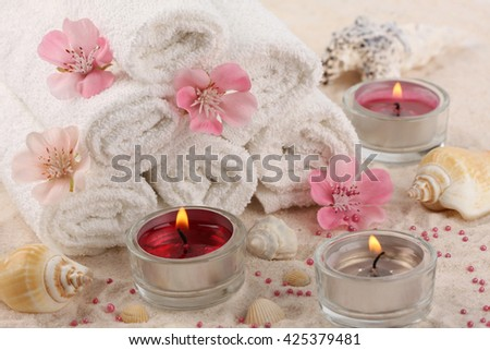 Spa composition - towels, aromatic flowers and candles, shells on white sand - stock photo