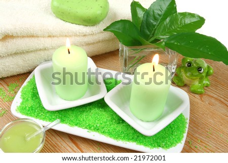 Spa composition - white towels, green soap, candle and conditioner in small bowl. Lemon leaves.