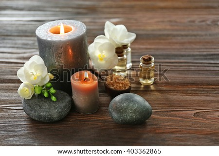 Spa composition with candle, pebbles and aroma oil on wooden background