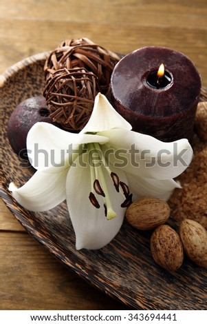 Spa composition with lily flower, candle and sea salt in bowl on wooden table - stock photo