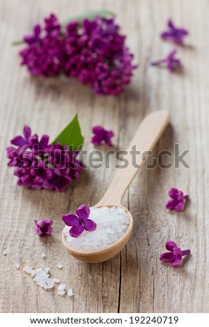 Spa composition with sea salt bath in wooden spoon and lilac flowers on a rustic surface, aromatherapy concept - stock photo