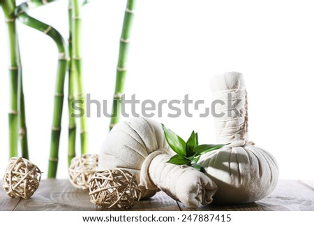 Spa compress balls with bamboo sticks isolated on white
