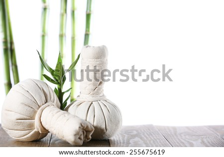 Spa compress balls with bamboo sticks isolated on white - stock photo