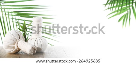 Spa compress balls with green leaves isolated on white - stock photo