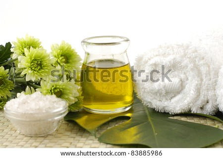spa concept- bath salt in bowl with green flower and essential oil and towel on mat - stock photo
