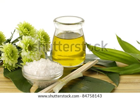 spa concept- bath salt in bowl with green flower and essential oil on mat - stock photo