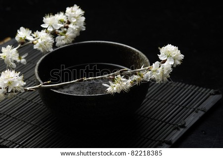 Spa Concept- blossom sakura with water on mat - stock photo
