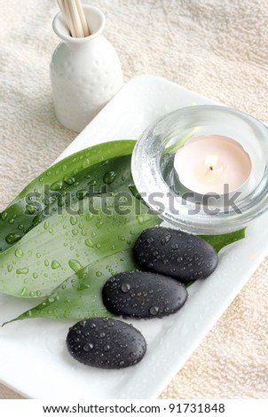 Spa Concept: bottle of essential oil, massage stones and candles - stock photo