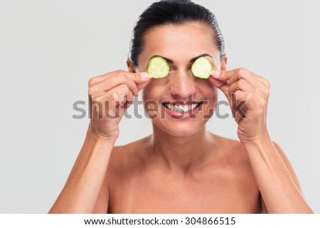 Spa concept. Happy woman covering her eyes with cucumber isolated on a white background - stock photo
