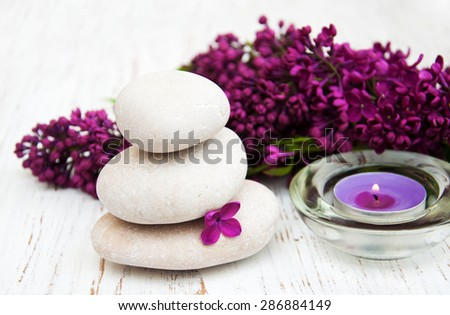 Spa concept - massage stones, candle and lilac flowers - stock photo