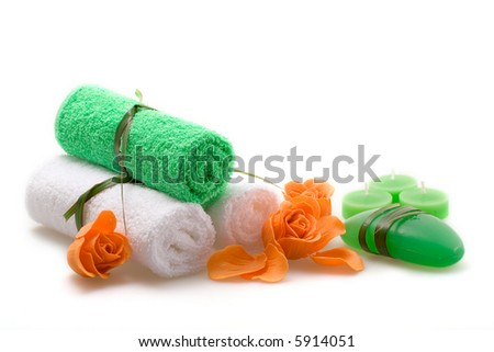 Spa concept of green color: the towel, soap and candles over white background