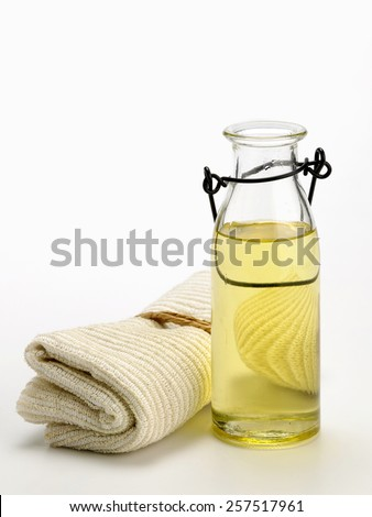 spa concept of massage oil and towel - stock photo