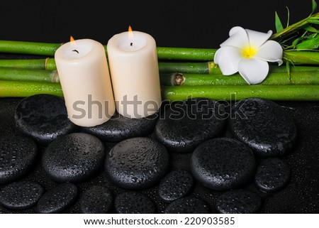 spa concept of zen basalt stones, white flower frangipani, candles and natural bamboo with dew - stock photo