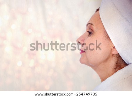 Spa concept portrait. Aged good looking woman with white towel on her head - stock photo