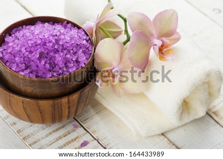 Spa concept. Sea salt in bowl with flowers and towel on white wooden background. Selective focus.