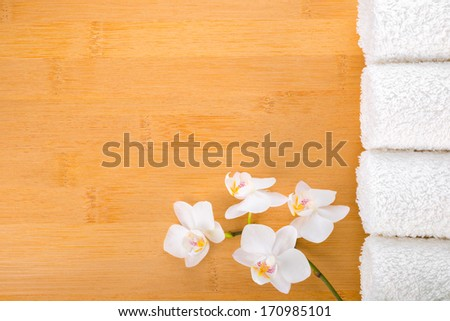 spa concept, white orchid and white towels on the bamboo background  - stock photo