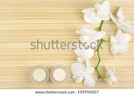 SPA concept: white orchids and candles on mat.