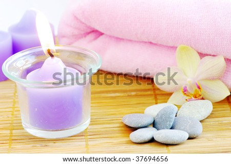 spa concept with candles orchids towels and stones on wet wooden background - stock photo
