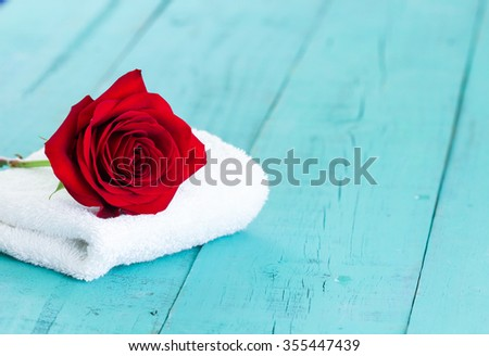 Spa concept with single red rose on white towel with antique rustic teal blue wood background - stock photo