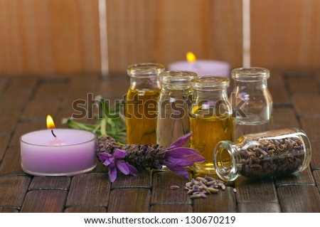 Spa concept with with aromatic lavender, candles and massage oils - stock photo