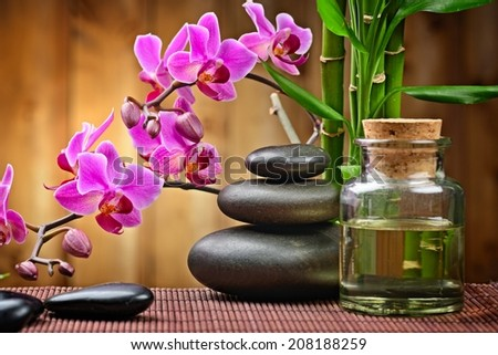 spa concept with zen basalt stones and orchid on the wood  - stock photo