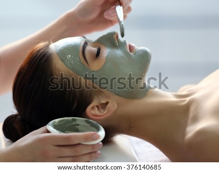 Spa concept. Young woman with nutrient facial mask in beauty salon, close up - stock photo