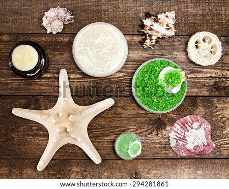 Spa cosmetics and accessories: sea salt, loofah, skin care cream, natural scrubs with shells and starfish on wooden planks. Top view. High contrast - stock photo