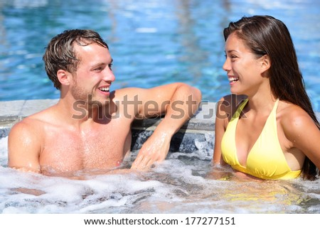 Spa couple happy in wellness hot tub jacuzzi laughing having fun being in love. Happy young lovers on honeymoon vacation travel to luxury resort spa retreat. Handsome man and beautiful asian woman.