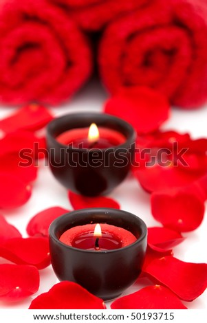 Spa decor with candle, towel and red rose petals