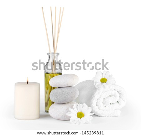 spa decoration with stones, daisies, candle and a bottle with massage oil on a white background with clipping path - stock photo