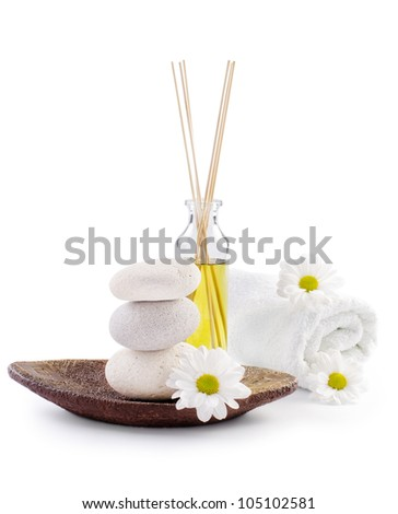 spa decoration with white chrysanthemum flowers, spa stones and a bottle with massage oil - stock photo