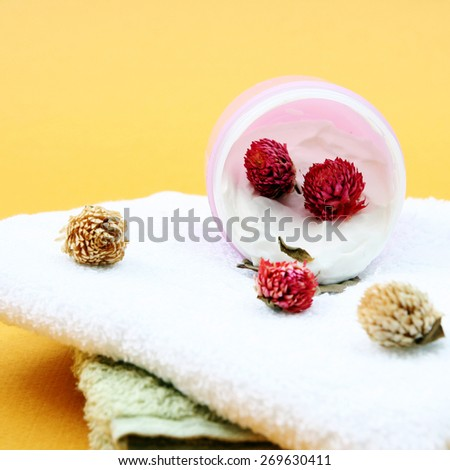 Spa essentials (cream, white towel and pink flowers) - stock photo