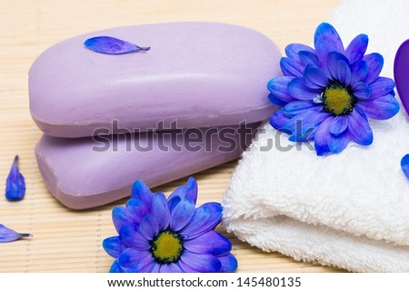 spa essentials, soap and towel with blue flowers  - stock photo
