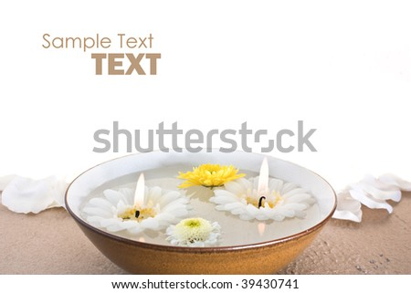 spa flowers and candles in a water bowl with white copy space - stock photo
