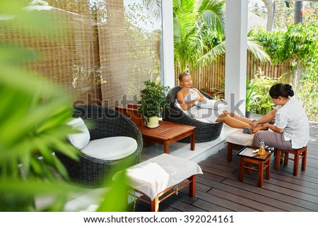 Spa Foot Therapy. Woman Body Care Treatment. Masseur Massaging Young Female Feet With Aromatherapy Oil Outside In Spa Salon Garden. Relaxing Recreational Massage. Skin Care, Beauty Procedure Concept - stock photo