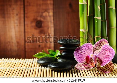 spa frame from bamboo grove, pink orchid and black zen stones on the old wooden backgroun - stock photo