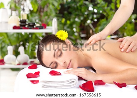 Spa girl. Beautiful young woman with flower in head lying on front while massage therapist massaging her back - stock photo
