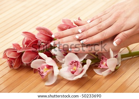 Spa hands over bamboo mat - stock photo