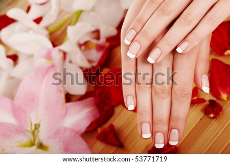 Spa hands over floral background - stock photo