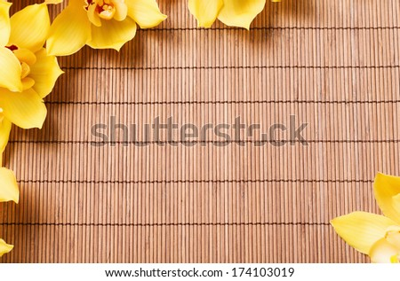 spa, health and beauty concept - closeup of orchid flowers on bamboo mat - stock photo