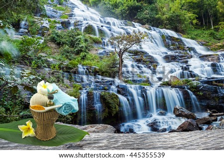Spa herbal compressing ball,white frangipani flower,turmeric powder in white spoon massage oil and blue fabric in bamboo basket and green leaf tree on wooden and waterfall background. - stock photo