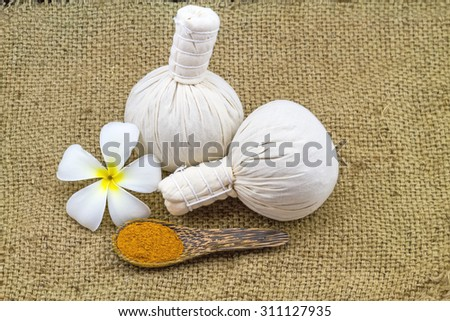 Spa herbal compressing ball , white frangipani flowers (Plumeria spp , Apocynaceae, Pagoda tree, Temple tree) and turmeric powder  in wooden spoon on brown sack fabric background - stock photo