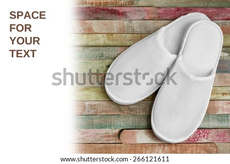 Spa, hotel - home slippers close on color planks wooden background with space for text - easy remove text - stock photo