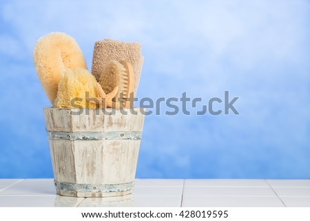 Spa items in wooden bucket with fresh blue background - plenty of copy space for advertising - stock photo