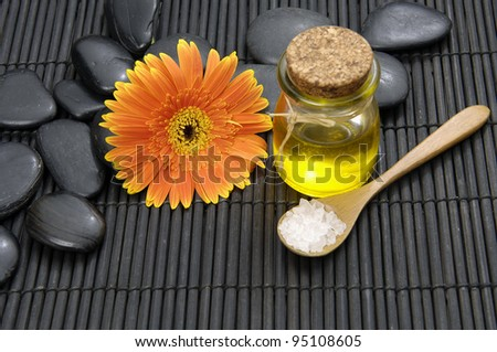 Spa life setting(gerbera and stones, Massage oil ,spoon in salt) - stock photo