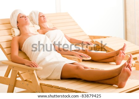 Spa luxury relax room two beautiful women lying on sun-beds - stock photo