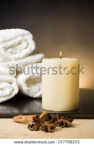Spa massage border background with towel stacked and candle with spices and cinnamon flavor, warm atmosphere - stock photo