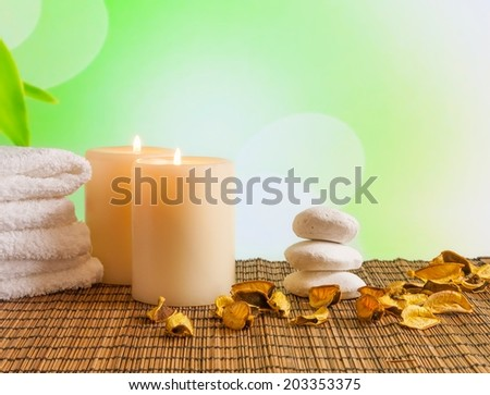 Spa massage border background with towel stacked, candles and perfumed leaves on bamboo table - stock photo