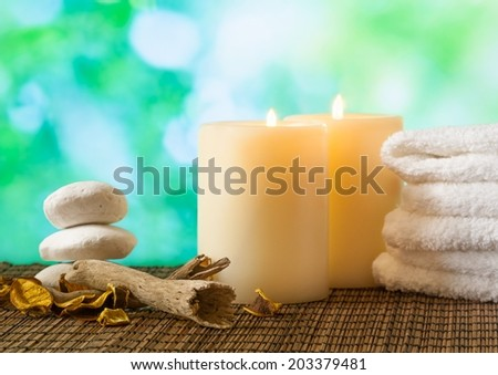 Spa massage border background with towel stacked, candles and perfumed leaves on green bokeh background